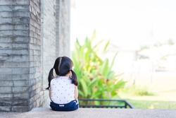 Back view of Little baby toddler girl sulk and sitting alone watching garden in school.Concept of bullied school girl.First day of school.Sad girl miss her mother in school.