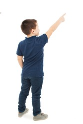 Back view of little boy points at wall. Rear view. Isolated on white background