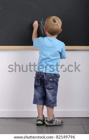 back view of little boy writing on a blackboard