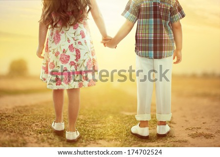 Back view of little girl and boy holding hands at sunset Love concept