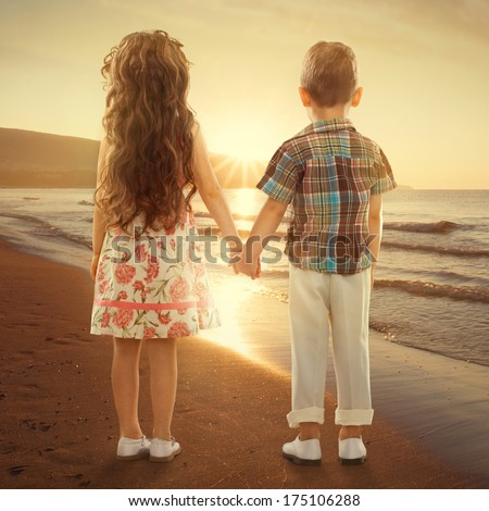 Back view of little girl and boy holding hands at sunset. Love, friendship concept