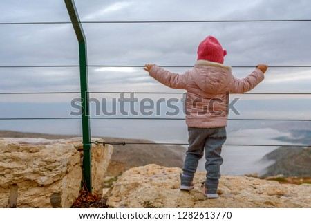 Back view of little girl at the top the Lookout observation deck view point beautiful nature. Look of foggy hills, mountain, valley at winter sunset.   #1282613770