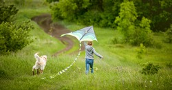 Back view of little girl with cute dog flying colorful kite on spring nature