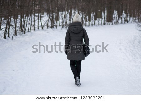 Back view of lonely girl walking on the road of snow in winter park. Silhoette of person. Period of depression and search of life meaning. #1283095201