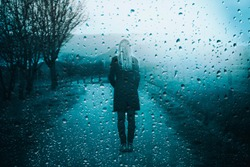 Back view of lonely sad woman standing outdoor with artistic rain drops background.