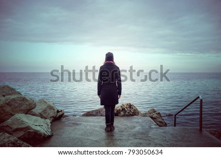 back view of lonely woman looking the see, loneliness concept in winter season