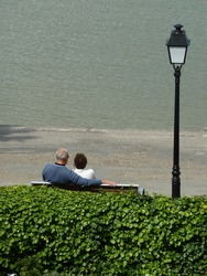 Back view of lovers sitting on a bench. They're looking the beautiful landscape of Bay of Somme. France.