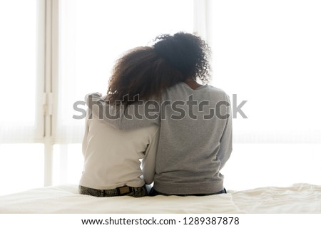 Back view of loving African American mother hug teen daughter sitting on bed, caring black mom embrace child, relaxing in bedroom looking in window, parent comfort teenager caressing at home