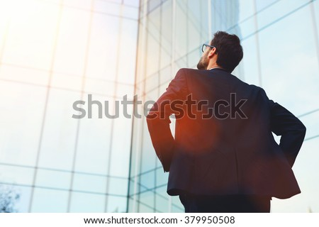 Back view of male architect looking on designed by him modern bank building while standing outside, intelligent young businessman dreaming about prosperity of his company after important meeting