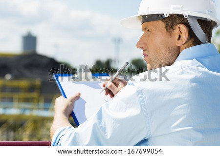 Back view of male architect with clipboard at construction site #167699054