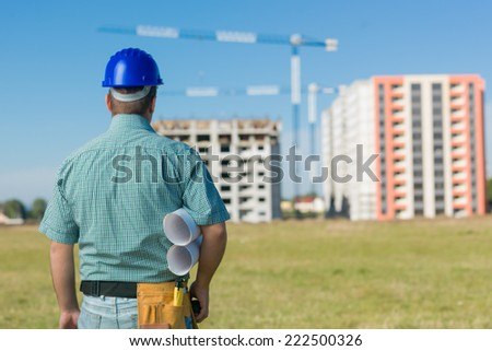 back view of male civil engineer holding plans, looking at building project in progress