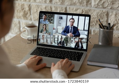 Back view of male employee sit at desk speak talk on video call on laptop with diverse colleagues, businessman have computer webcam conference conversation with coworkers or business partners