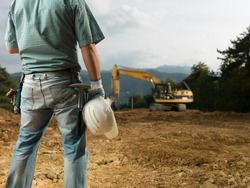 back view of male engineer standing on construction site holding white hardhat