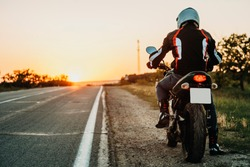 Back view of male in protective jacket, boots and helmet riding off roadside at sunset on empty highway backlit background