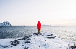 Back view of male in winter trendy red coat standing on coastline with ice and snow near nordic calm sea water, man exploring scandinavian fjordlands and lake for fishing