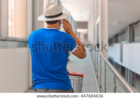 Back view of male person walking talking on mobile smart phone during  shopping. Cart on 803e8c2a1cb3