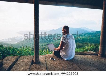 Back view of male tourist blogger work remote on laptop computer while enjoying beautiful nature landscape view in Asia.Young man using online banking for sending money everywhere you are from netbook