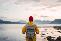 Back view of male tourist with rucksack standing on coast in front of great mountain massif while journey.  Man traveler wearing yellow jacket with backpack explore Scandinavia nature. Wanderlust