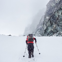 Back view of male traveler with backpack walking through the snow in winter mountains. Backpacker with trekking sticks hiking alone and heading to mountaintop. Concept of winter travelling and hiking