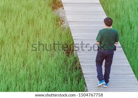 Back view of male walk and take photography along the bamboo path that crossed through the fields in the evening before the sun set down on the horizon. #1504767758