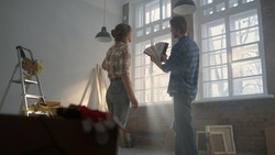 Back view of man and woman discussing decorate details in new house. Young family choosing pastel color for apartment walls indoors. Happy couple speaking about home repair questions inside.