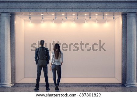 Back view of man and woman looking at illuminated clear storefront and columns in night city. Advertisement and commerce concept. Mock up, 3D Rendering
