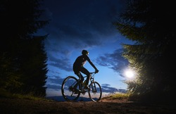 Back view of man cyclist riding bike under blue evening sky with clouds. Silhouette of bicyclist riding bicycle on the trail in night mountain forest. Concept of sport, biking and active leisure.