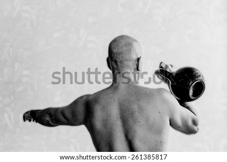 Back view of man doing exercises with kettlebell background. Black-and-white, lite blur background, horizontal