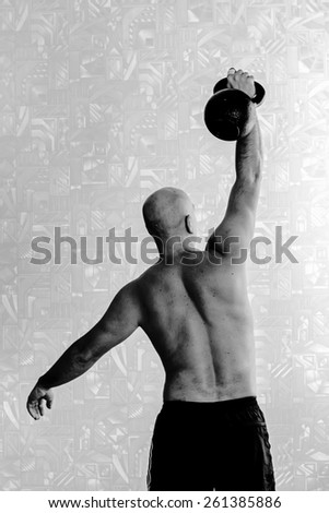 Back view of man doing workout with kettlebell background. Black-and-white, vertical