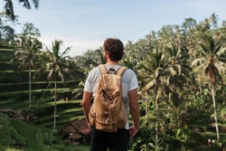 Back view of man explorer  with travel backpack enjoying natural environment of green  rise  plantation during trip in Bali .Tourist with rucksack standing in asia wild valley during treck.