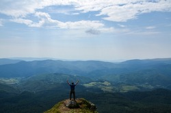 Back view of man hiker standing on the rock in the beautiful mountains with rising hands and enjoying amazing landscape, summer time. Carpathian Mountains, Ukraine