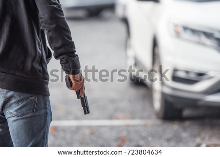 Back view of man holding a gun in car park.