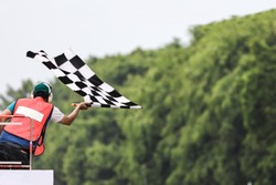 Back view of man holding checkered race flag