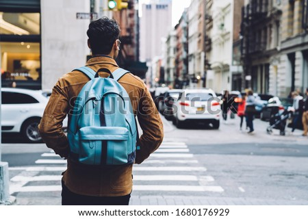 Back view of man in jacket and earphones with black hair and blue backpack walking on street of New York city Stockfoto ©
