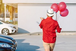 Back view of   man in red shirt holding red balloons from the car park to join the party in the afternoon.