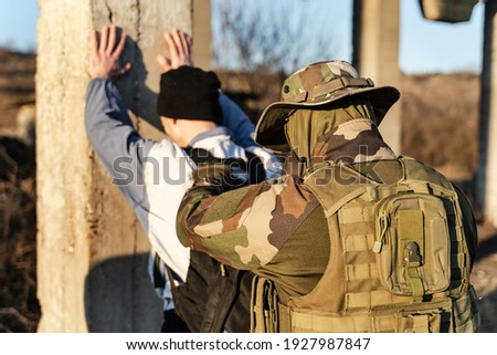 Back view of man in uniform unknown military soldier or special forces police arresting and searching criminal illegal migrant or terrorist in sunny day