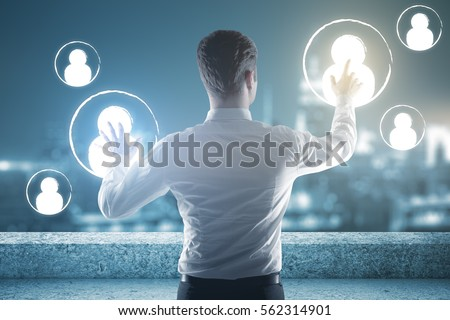 Back view of man on rooftop managing people icons. HR concept