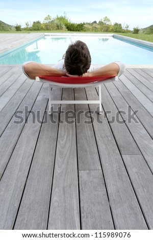 Back view of man relaxing in long chair