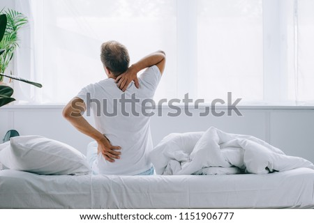 back view of man sitting on bed and suffering from back pain #1151906777