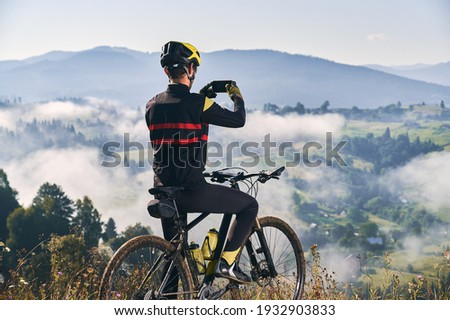 Back view of man sitting on bicycle and talking mountain photo with smartphone. Male bicyclist holding cellphone and taking picture of beautiful misty hills. Concept of sport, cycling and photography.