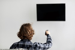 Back-View Of Man Watching TV Pointing Remote Control At Flatscreen Plasma Television Set Switching Channels Sitting On Couch At Home. Viewer Enjoying TV Show Spending Evening Indoors. Selective Focus