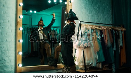 Back view of man wearing costume of pirate and standing in front of mirror in dressing room practicing scene from performance ストックフォト ©