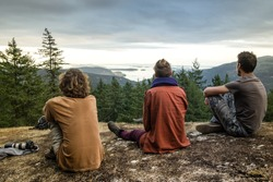 Back view of men travelers sitting and relaxing during breathtaking on mountain top, Vancouver Island. three friends enjoying nature landscape. Travel outdoor wanderlust hiking lifestyle concept.