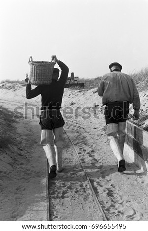 Back view of men walking and wearing rain boots