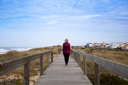 Back view of middle-aged woman walking alone on boardwalk at the beach and distant houses. Autumn walk by the sea near the neighborhood. Health, social distancing and retirement concepts