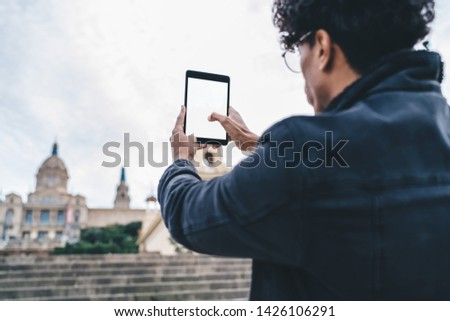 Back view of millennial male tourist using modern blank touch pad with copy space for advertising for clicking photos of city landscape in historic center, travel man photographing buildings #1426106291