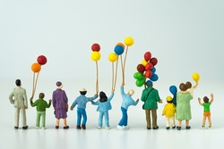 back view of miniature happy family holding balloons with white background as happy family concept.