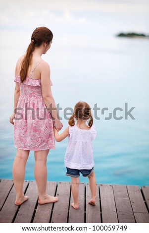Back view of mother and daughter enjoying sea views