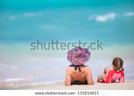 Back view of mother and daughter on a tropical beach