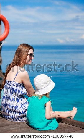 Back view of mother and daughter sitting on wooden dock